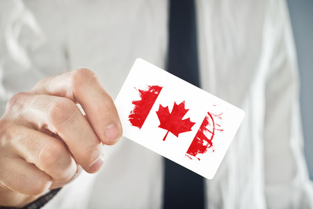 Canadian Businessman holding business card with Canada Flag. International cooperation, investments, business opportunites concept. Stock Photo