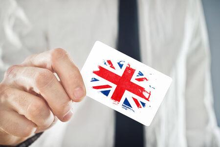 britain flag: El hombre de negocios de tarjetas de negocios brit�nico celebraci�n con la bandera de Gran Breta�a. La cooperaci�n internacional, las inversiones, Oportunidades de negocios concepto. Foto de archivo