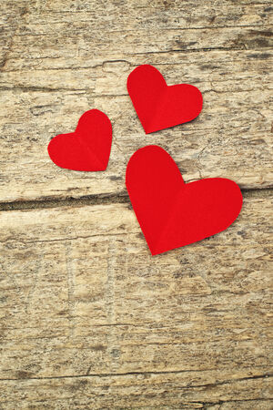 Paper hearts on old wood background. Heart shape red paper note with copy space. photo
