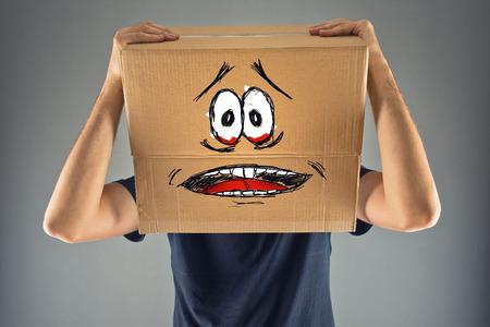 Homme avec boîte en carton sur la tête et terrifié regard skethed. terrifié; congelés; l'homme a peur.