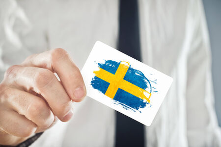 foreign nation: Swedish Businessman holding business card with Sweden Flag. International cooperation, investments, business opportunities concept. Stock Photo