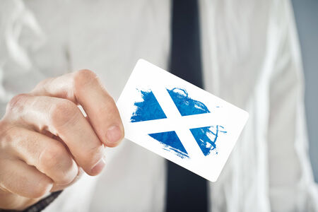 scotish: Scotish Businessman holding business card with Scotland Flag. International cooperation, investments, business opportunities concept. Stock Photo
