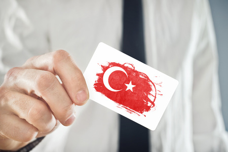 turkish flag: Turkish Businessman holding business card with Turkey Flag. International cooperation, investments, business opportunities concept.