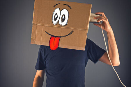 tin can telephone: Man with cardboard box on his head using tin can telephone for conversation. Happy face expression.