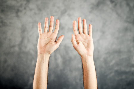 Caucasian male open hands raised for surrender on grunge background