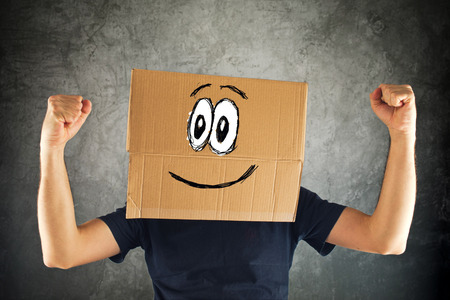 head for: Happy smiling man with cardboard box on his head and raised fists for victory. Concept of winning.