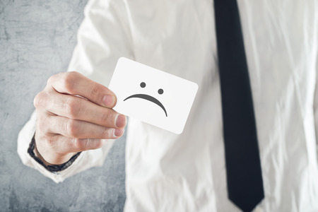 pathetic: Businessman holding business card with sad face printed. Unhappy businessman, office situation.