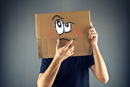 Man thinking with cardboard box on his head with serious face expression.  photo