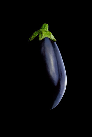 eggplants: Eggplant or aubergine on black background. This vegetable is also known as melongene, garden egg or guinea squash.