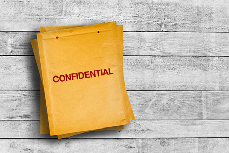confidential: Confidential stmp on yellow envelope placed on wooden table