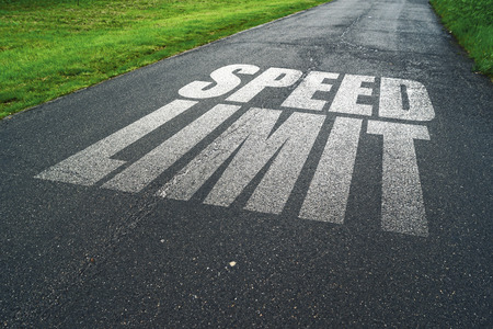 regulations: Speed Limit message reminder on asphalt road. Concept of safe driving and preventing traffic accident.
