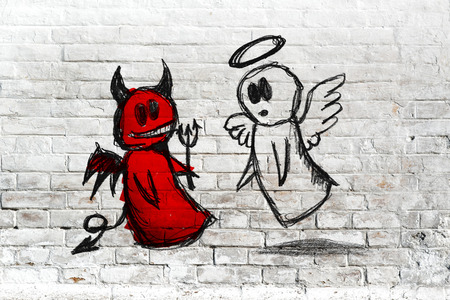 Doodle drawing of angel and devil fighting on white brick wall. Concept of conscience; decisions, uncertainty, moral dilemma; fight of good and evil.