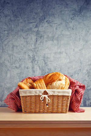 Delicious bread in wicker basket on kitchen table Stock Photo