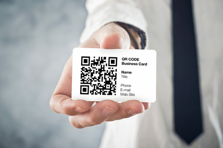 Businessman holding QR code business card with personal data. Modern technology concept. Stockfoto