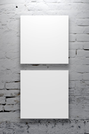 Two Square Posters hanging on the art gallery white wall. photo