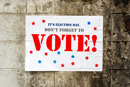reminding: Election day poster reminding you to Vote on grunge street wall Stock Photo