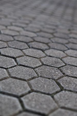 empedrado: Pavimento de adoquines con enfoque selectivo y profundidad de campo. Fondo de la calle urbana. Foto de archivo