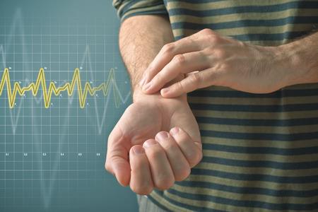 salud publica: Hombre que controla su pulso presionando la muñeca con los dedos. Las cuestiones de salud concepto.