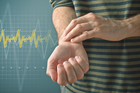 public health: Man checking his pulse by pressing the wrist with fingers. Health issues concept.