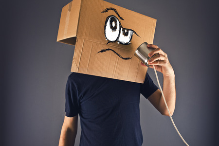 Man with cardboard box on his head using tin can telephone for conversation. Angry face expression. photo
