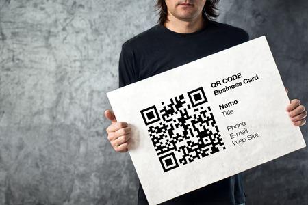 datos personales: Hombre que sostiene la tarjeta de visita de QR c�digo con los datos personales. Concepto de la tecnolog�a moderna.