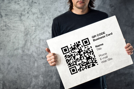 Man holding QR code business card with personal data. Modern technology concept.