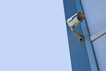 under surveillance: Security CCTV camera. Security camera mounted on the wall protecting industrial building. Stock Photo