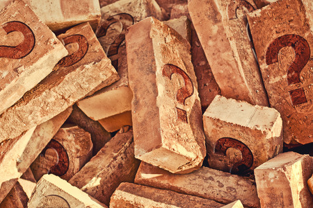 costruction: Pile of bricks with question amrks. Costruction material heap. Stock Photo