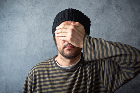 Portrait of casual man covering eyes on dark gray grungy background.