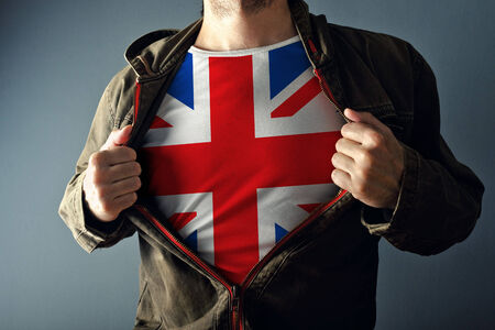 national hero: Man stretching jacket to reveal shirt with Great Britain flag printed. Concept of patriotism and national team supporting.