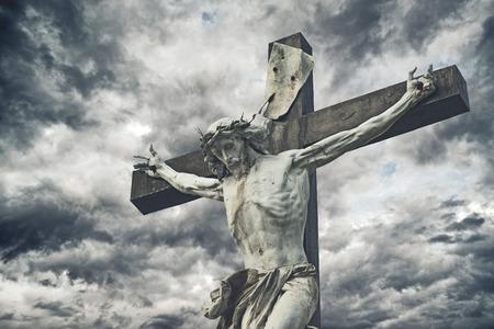 Kruisiging. Christelijke kruis met Jezus Christus standbeeld op stormachtige wolken. religie en spiritualiteit concept. Stockfoto