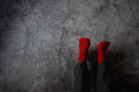 topsyturvy: Legs up the wall, putting feet up. Man wearing red socks in relaxing yoga pose with his legs on the wall.