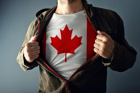 citizens: Man stretching jacket to reveal shirt with Canada flag printed. Concept of patriotism and national team supporting.