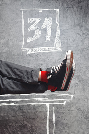 end month: Man in sneakers with his legs on the table. Lazy man at the end of the month having no work.