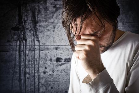Depressieve man huilen met de hand over zijn gezicht, op zoek boos en het tonen van berouw