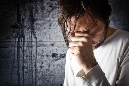Depressive man crying with hand covering his face, looking upset and showing remorse