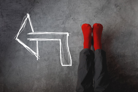 direction of the arrow: Male legs with red socks leaning on gray wall upside down with drawn direction arrow pointing to left. Youth education, youth guidance, student guide, consultation, advisory concept. Stock Photo