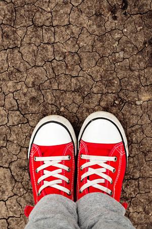 first step: Boy in rote Turnschuhe stehen auf dem Boden, von oben her. Aufwachsen mit ganzes Leben vor Konzept. Machen erste Schritt. Lizenzfreie Bilder