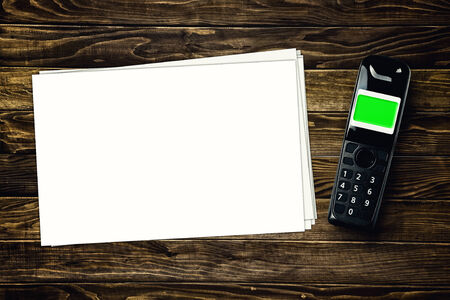 cordless phone: Wireless cordless phone and blank paper with copy space on wooden tabletop. Stock Photo