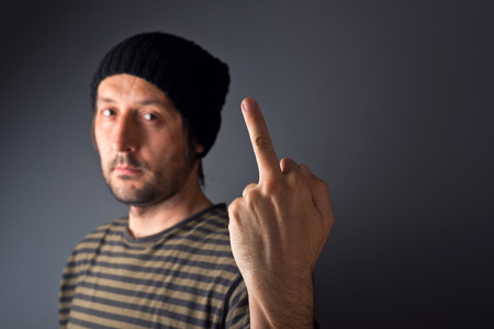Punk male is giving middle finger as rude gesture, selective focus on finger with shllow depth of field. photo