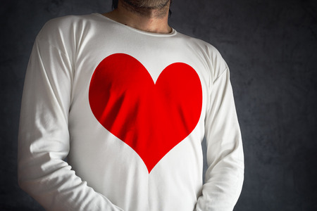 fondness: Man in white shirt with big red heart printed over his chest. Falling in love concept. Stock Photo