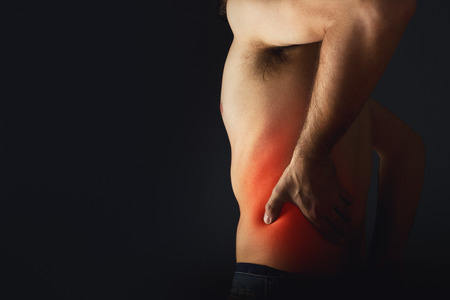 sciatic nerve: Backache. Pain in the lower back. Shirless man touching his back for the pain.