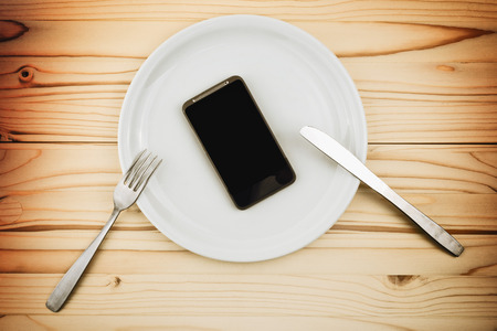 Mobile smart phone served as dinner on white plate. Concept of information absorption process.