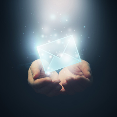 Hands with envelope. E-mail, global communications, mail or contact us concept. Selective focus on fingers. photo
