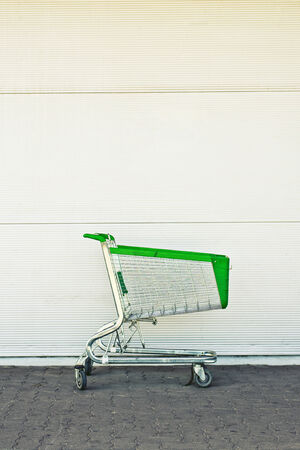 Empty Shopping Cart parked in front of large supermarket. Consumerism concept. photo