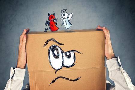 teufel engel: Gesch�ftsmann mit einem Karton auf dem Kopf mit Doodle Zeichnung von Engel und Teufel k�mpfen. Konzept des Gewissens; Entscheidungen, Unsicherheit, moralisches Dilemma; Kampf von Gut und B�se.