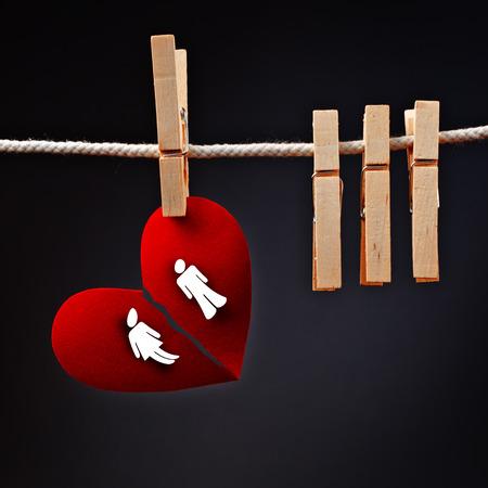 corazon roto: Pareja heterosexual rompiendo, imagen conceptual de amor el coraz�n de papel rasgado en dos, colgando de una cuerda con la ropa pin.