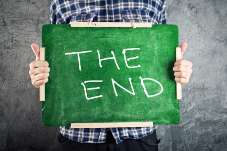 fin d annee: Homme tenant tableau vert avec le titre de la FIN. Fin du concept de l'ann�e scolaire.