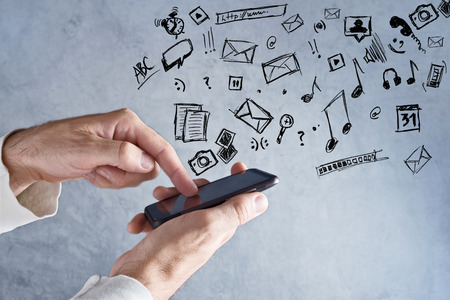 Touch screen mobile smart phone in male hands and doodle icons. Modern communication device is used for business tasks as well as for fun and enjoyment. photo