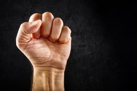 Riot protest fist raised in the air. Male clenched fist on dark grunge background.